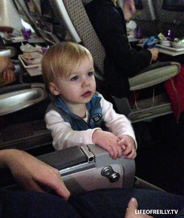 Let your little one stand in the aisle next to you. It's a long-haul flight, no-one will mind as long as they're not annoying them.